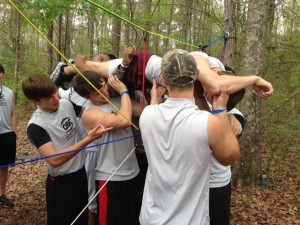 Members of the Quarterback Club help one another through a ropes course.